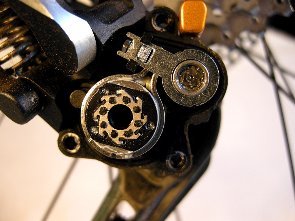 The one-way roller clutch is the larger cylinder at the lower left. The stainless steel band that encircles it is the friction brake. The adjustment wrench is stowed in the housing above the clutch. The friction adjustment nut is visible in the hex end of the tiny wrench.