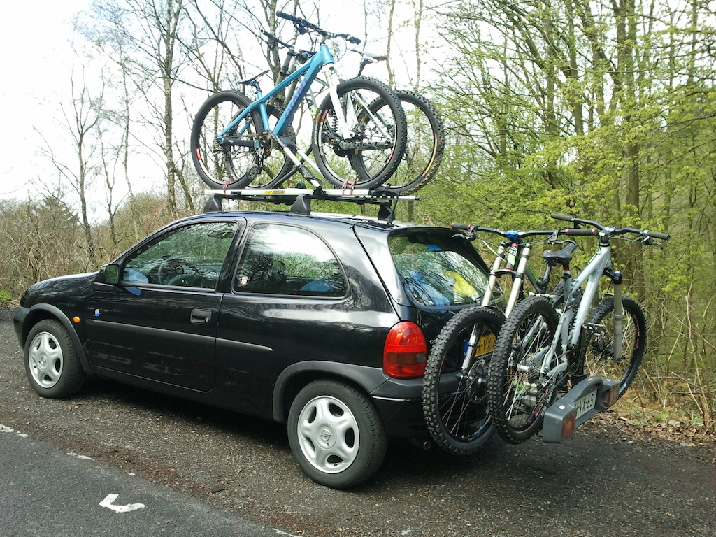 4 bikes and 3 persons with gear