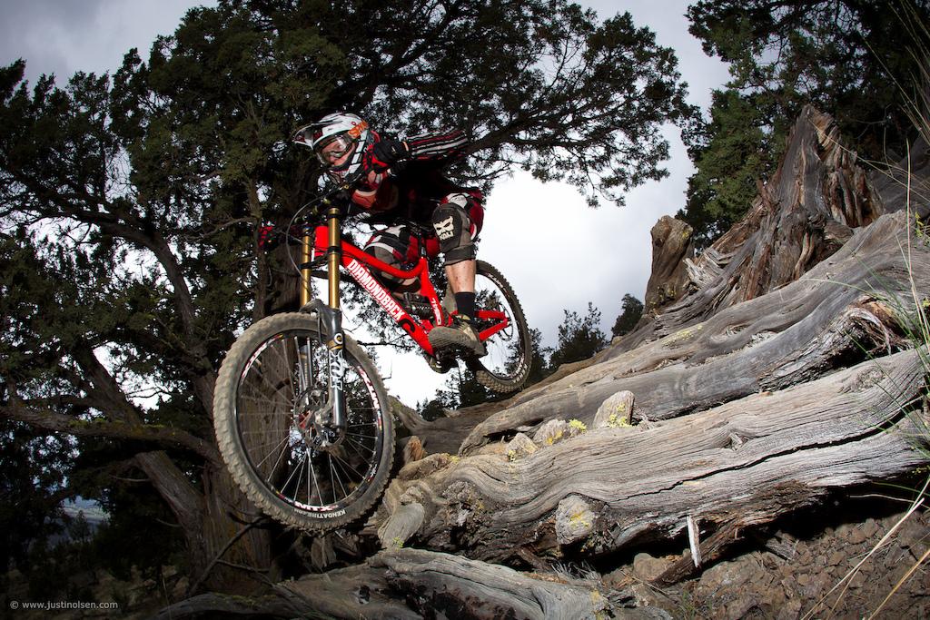 Kyle Thomas rallying the Diamondback prototype DH bike through the log bumps on the Cline Butte trail.
