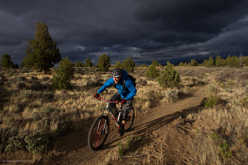 After 3 days of shooting in flat light and cloudy conditions it looked like the sun finally might come out. We headed out the the trail with our fingers crossed and it paid off. Jon Kennedy riding the storm out.