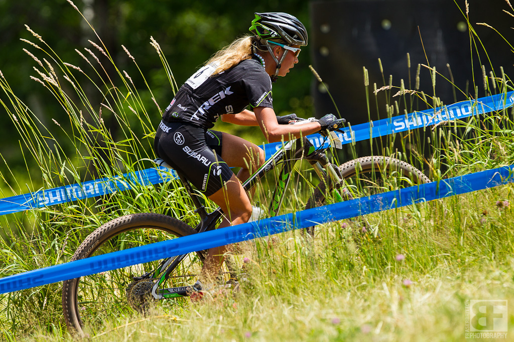 Emily Batty cranks here way through the tall grasses under high heat on XC day in Windham.