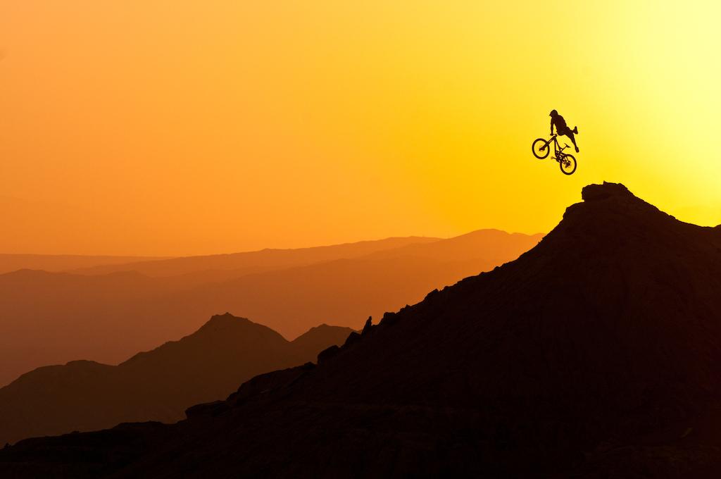 "Darren Berrecloth styles a ""no foot can"" off a booter into the gobi desert sunset"