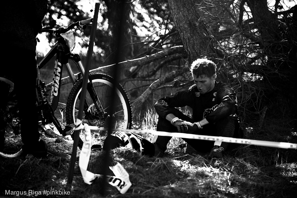 A rider sitting down and taking a deep breath to count his lucky star he s ok after casing hard on corner two of the DH course.