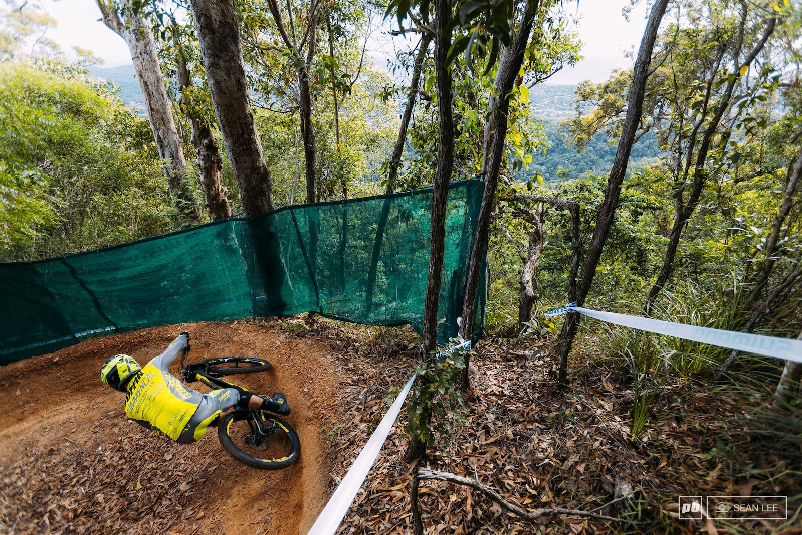 Thibaut Ruffin rails the first berms of the week looking down on the rainforest below.