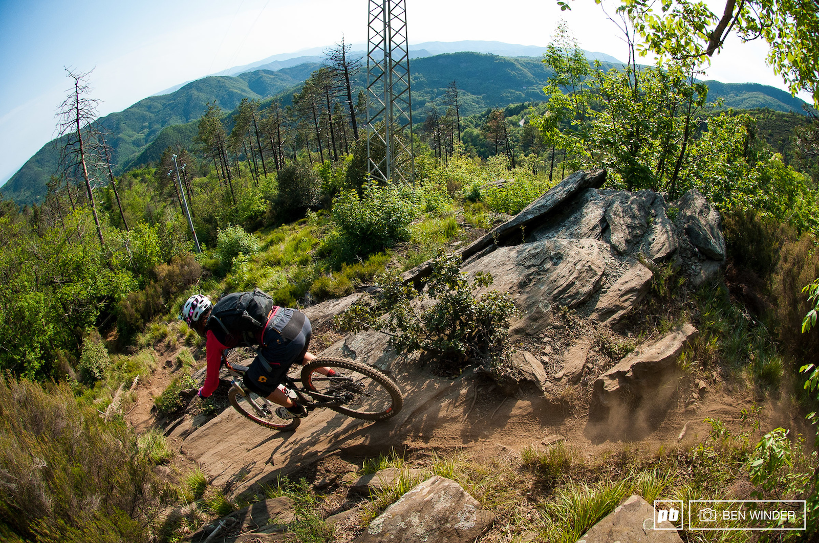 This is a moment when the trail comes out the woodland for a breath of fresh air but it s far from that for the riders descending into a super technical steep rock slab.