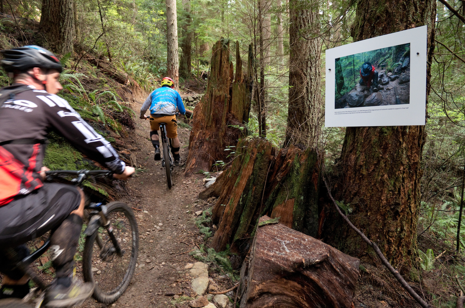 Riders viewing a print of Martin building the rock retaining wall holding up the corner in front of them.