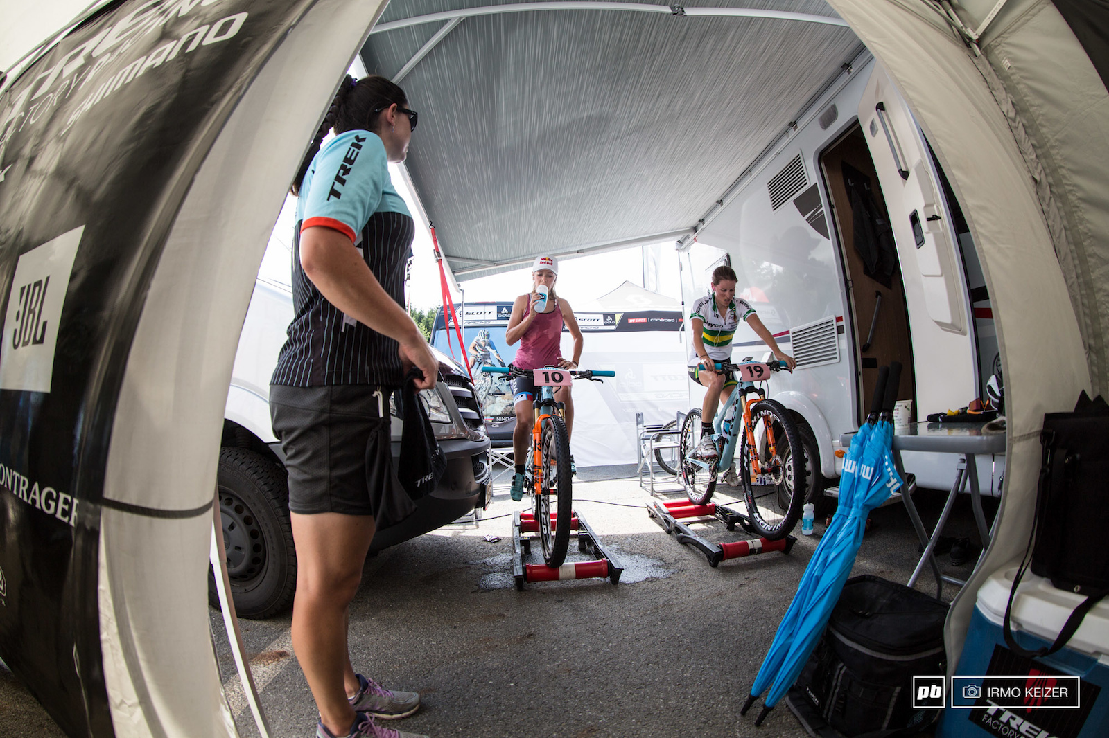 Emily Batty and Bec Henderson warming up at the back of the Trek Factory Racing team stand.