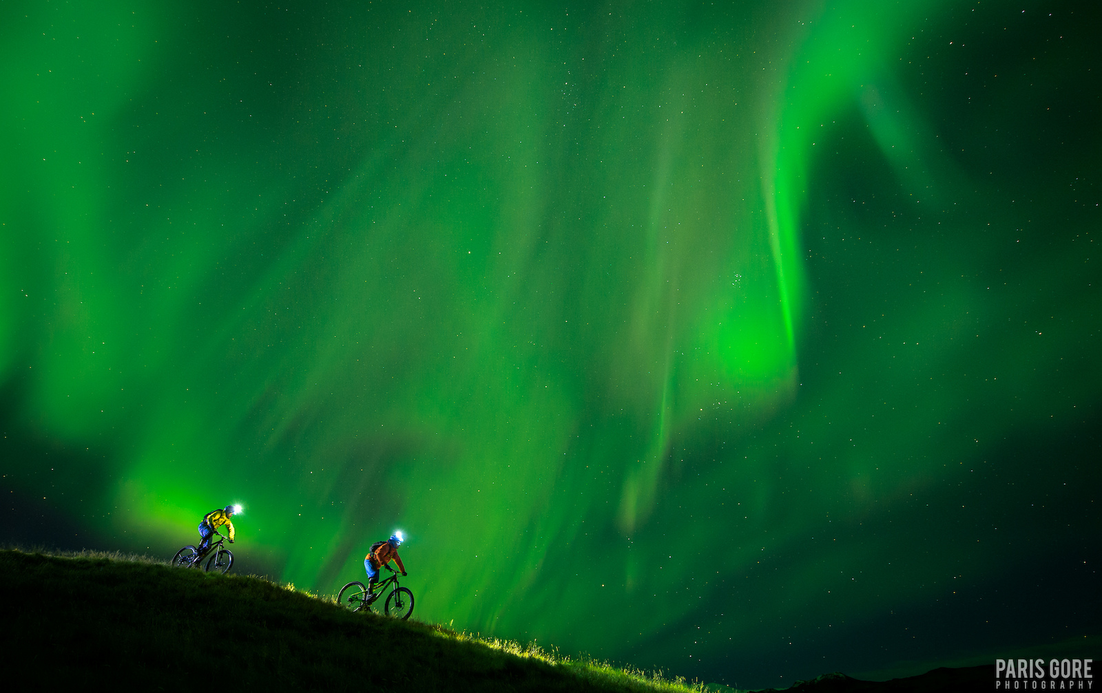 KC Deane and Geoff Gulevich in rsm rk Iceland underneath a spectactular Northern Lights show. The town of Reykjavik even demanded all lights be shut off in the city during this night due to the intensity of the showing here. Our crew went to Iceland with a vision to riding under the Northern Lights and we continually got shut down by weather. We photographed this the last night we were there on a 10 day trip and only saw the lights for two nights at the end of our trip departing our journey beneath a river of green in the skies.