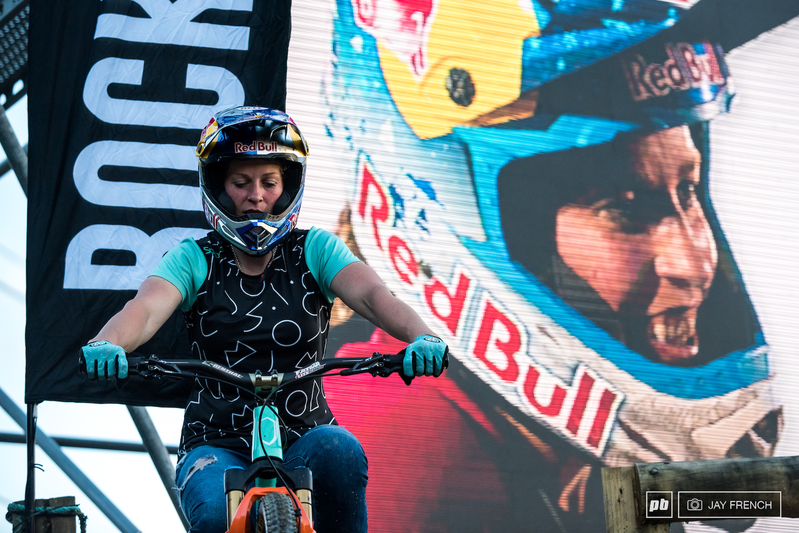 Jill sits patiently awaiting her heat while the big screen behind her pays tribute to her Queen of Crankworx.