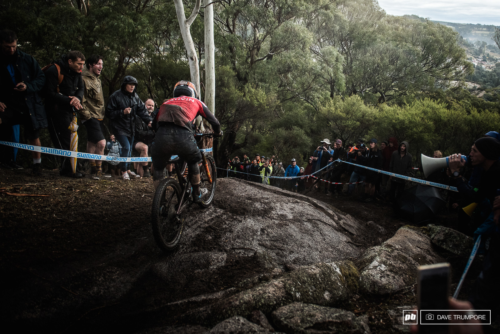 Remi Gauvin drops into the slick woods of stage 6 while the massive crowd looks on.