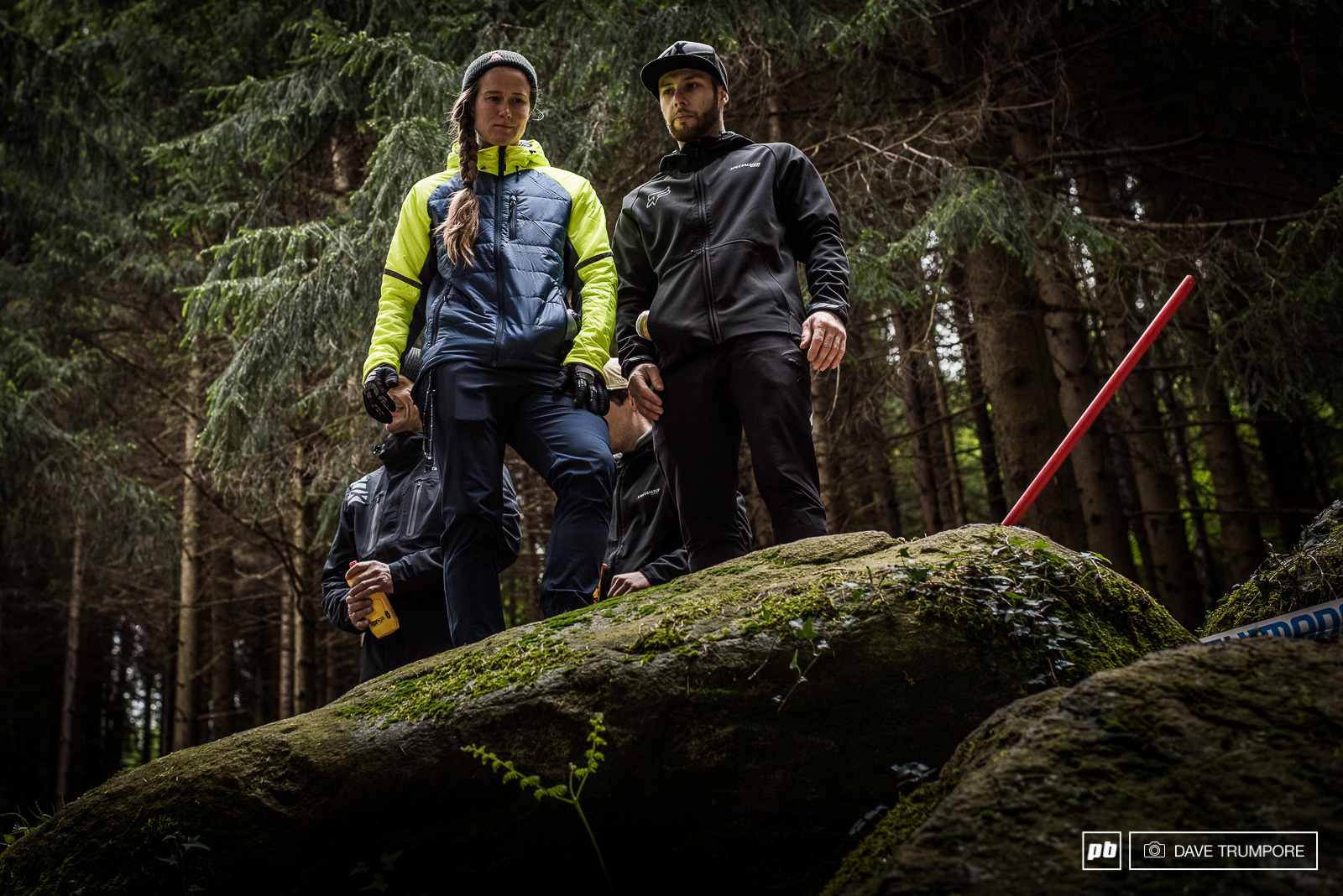 Miranda Miller and Mechanic Kevin Joly inspect the huck to flat that is actually more accurately described as a buck to off-camber flat full of big slippery roots.