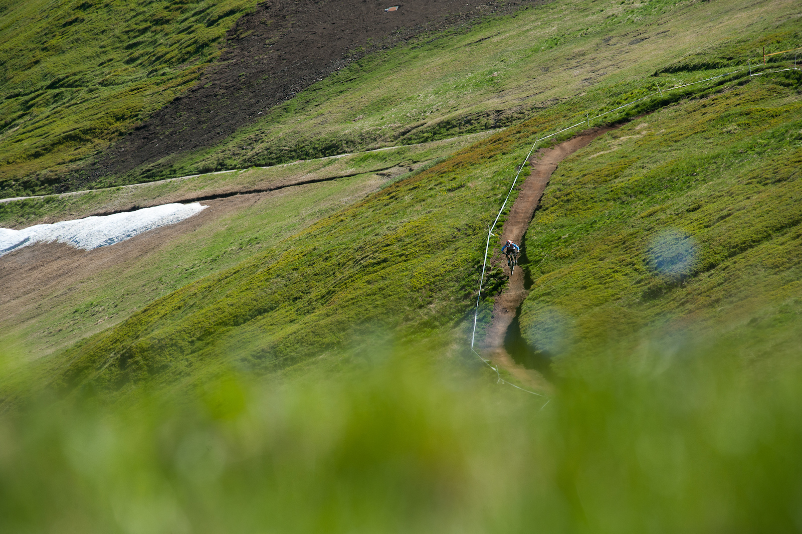 The top of stage one flows through open meadows on bike park trails.