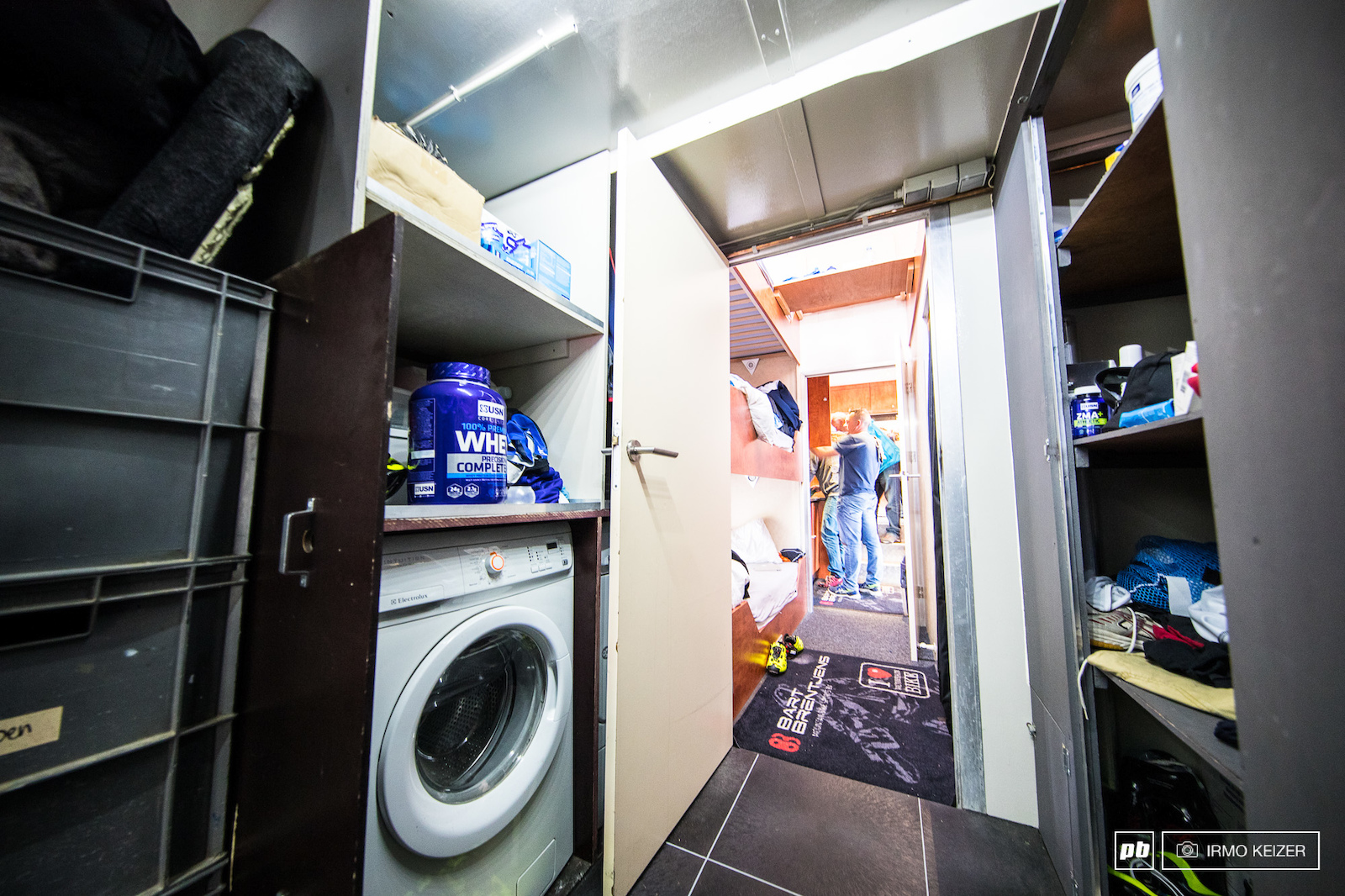 Spare parts provisions water bottles tyres and a washer dryer setup.