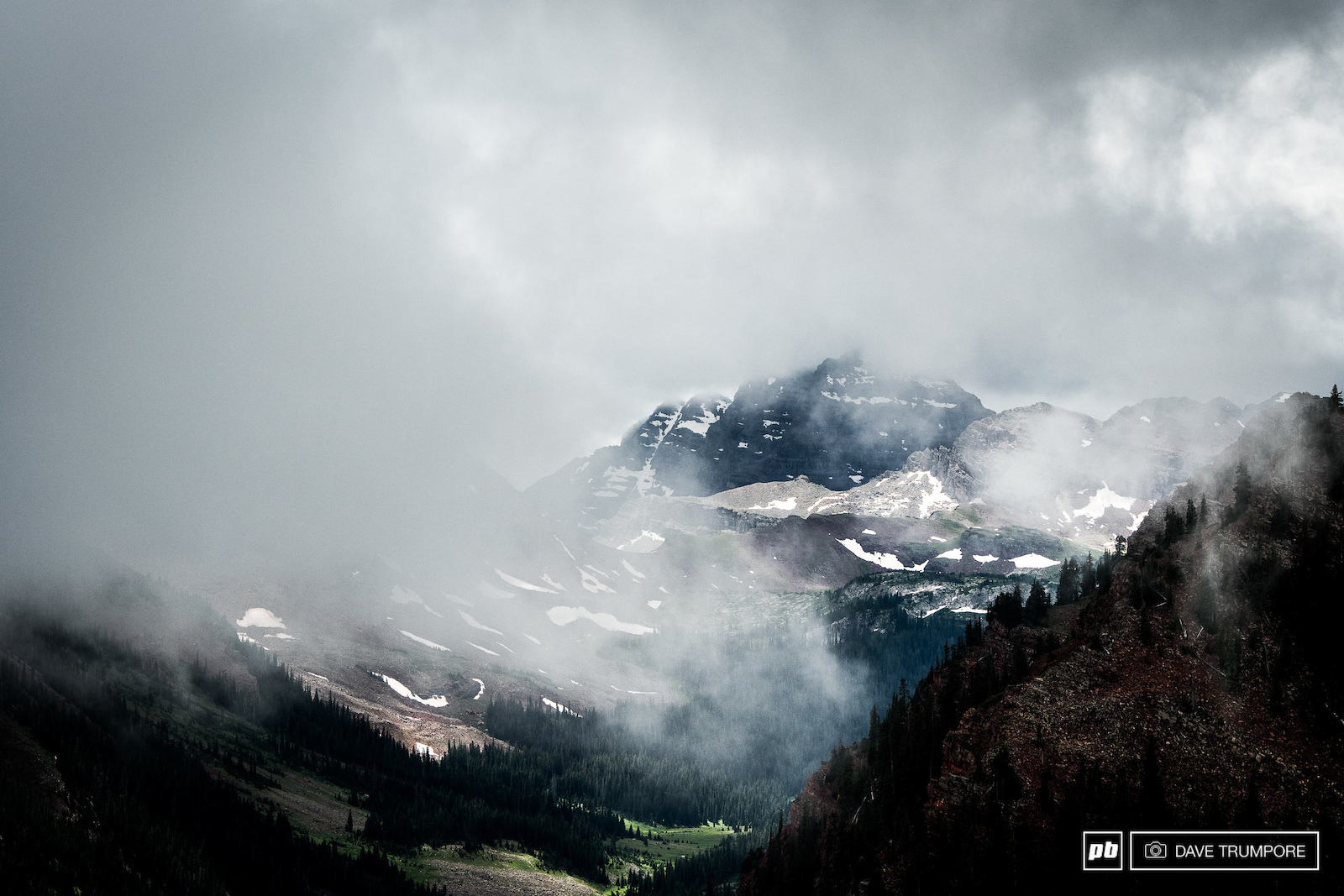 The iconic Maroon Bells peak through the cloud cover at the top of Stage 4.