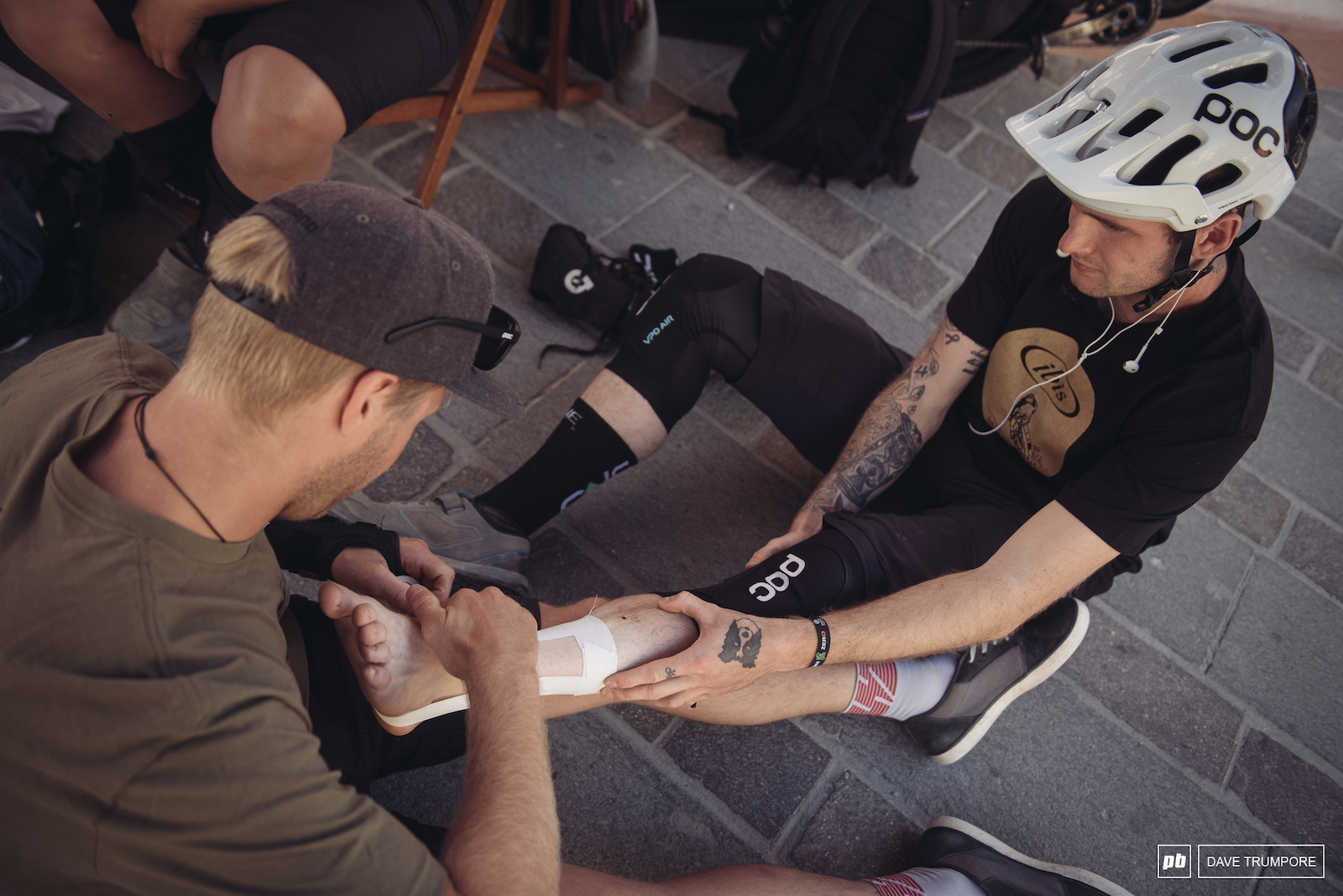 Robin Wallner tapes up the ankle of his injured teammate Lewis Buchanan before a long day in the saddle.