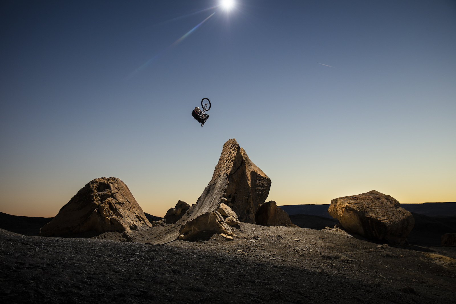 Brett Rheeder fully clicked off a natural rock quarter lit by overhead drone strobe during the filming of his segment in Big Water Utah for Return to Earth by Anthill Films.
