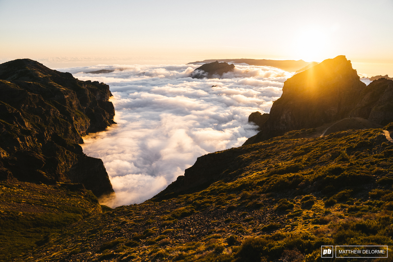 A sea of frothy white clouds meet Madeira s jagged higher peaks rolling up the cliffs and then falling back.