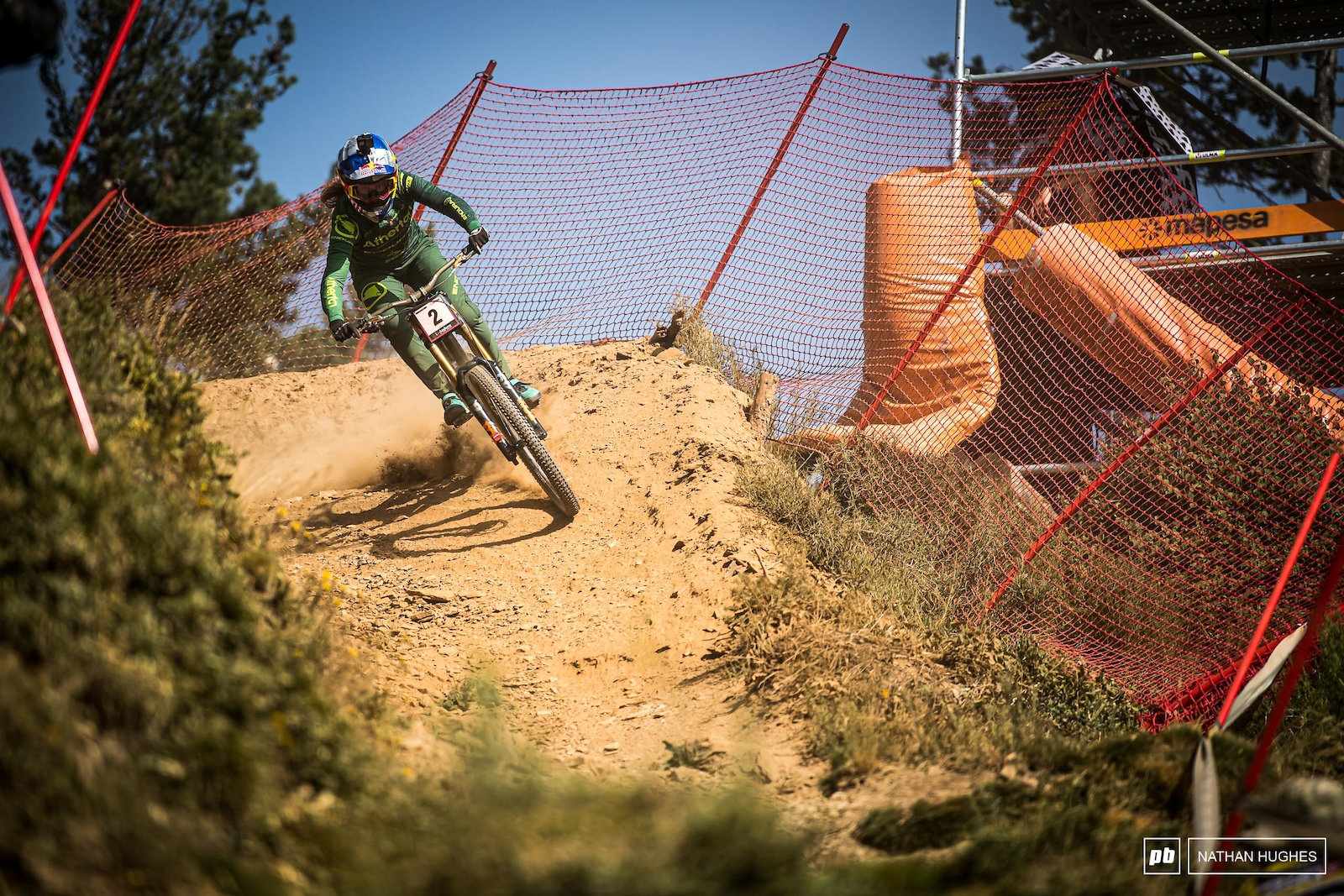 Rachel Atherton impacting on the hip-to-berm of the final open section before plunging deep down into the forest.