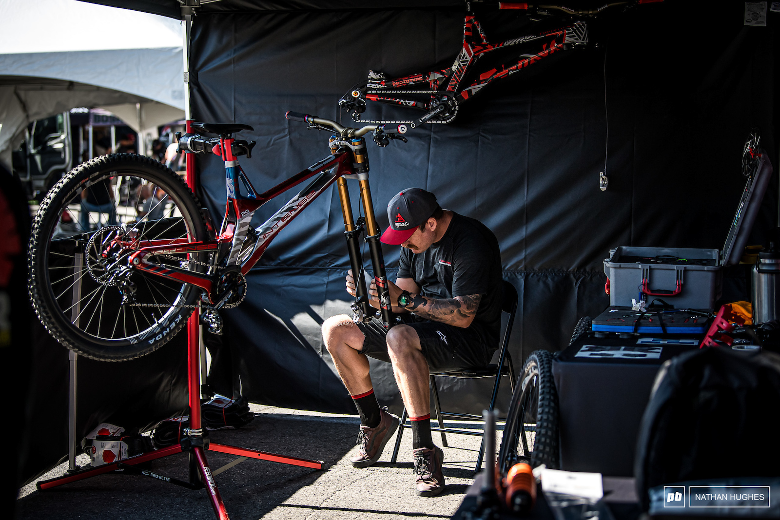 John Hall working on the bike that Aaron will almost certainly not ride this weekend while AG s race machine hangs on the tent wall behind.