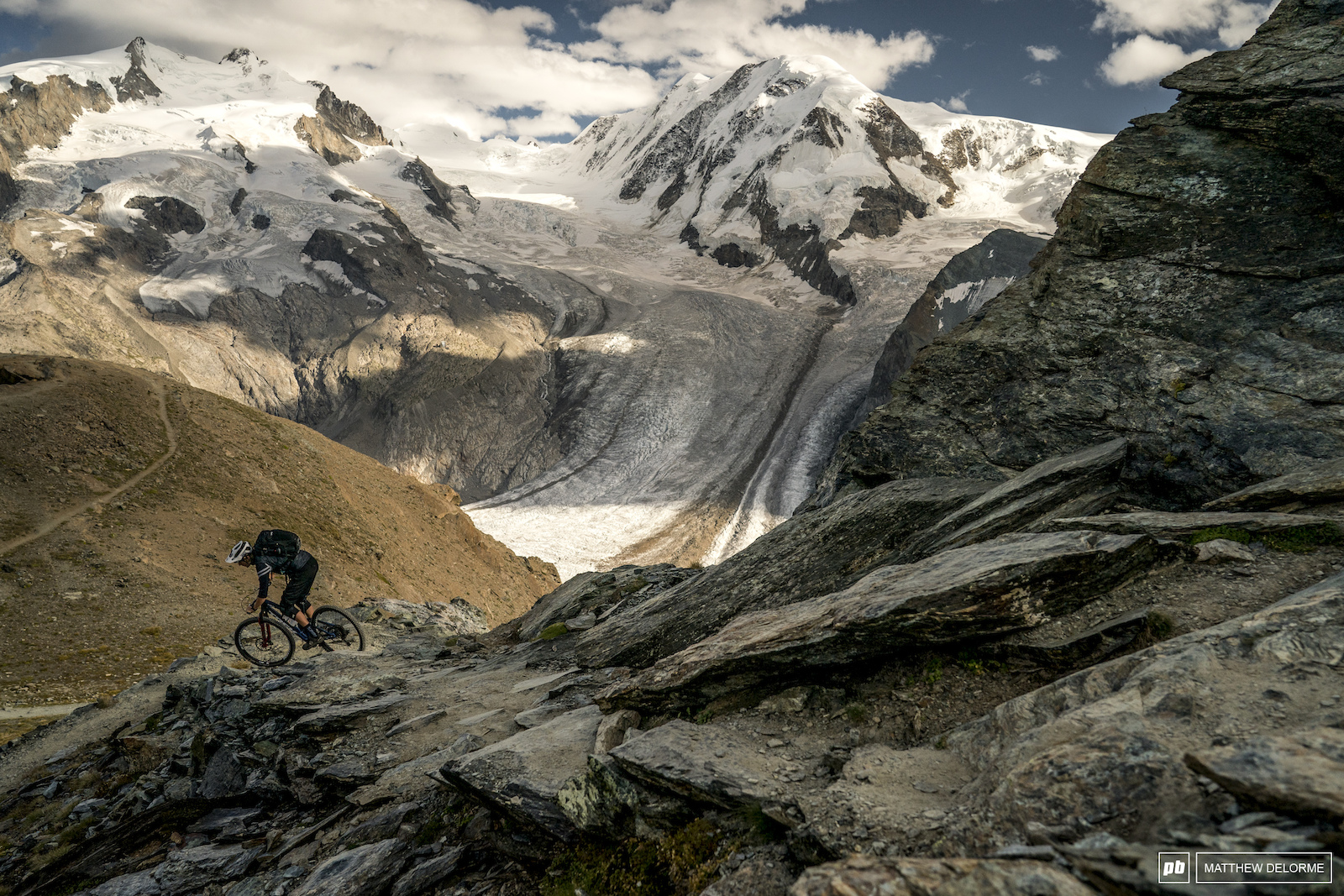 With Monte Rosa looking in the background TFR mechanic Andy Lund makes his way around a cliffed corner.