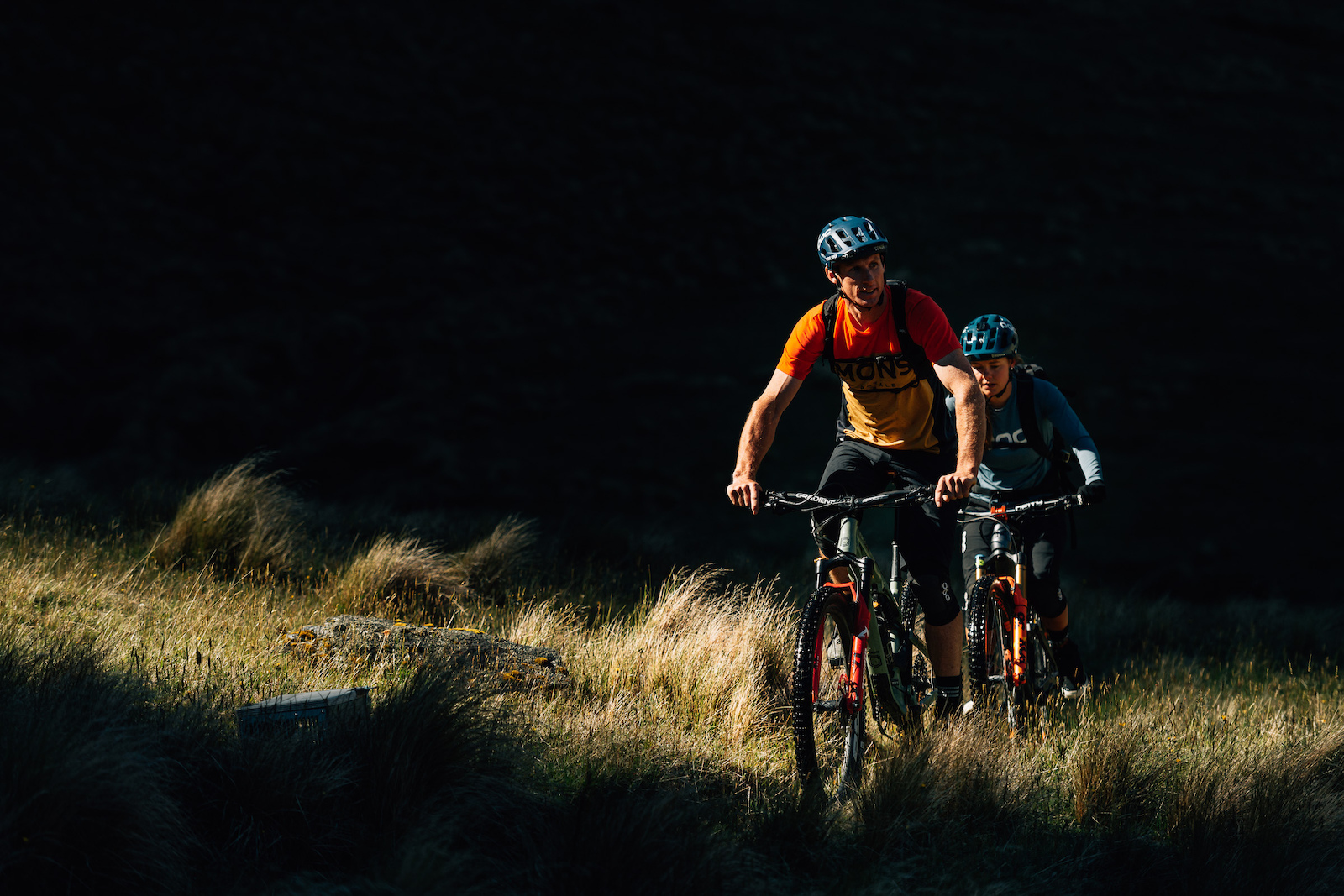 A shaft of light provided by a crack in the mountain illuminates the riders.