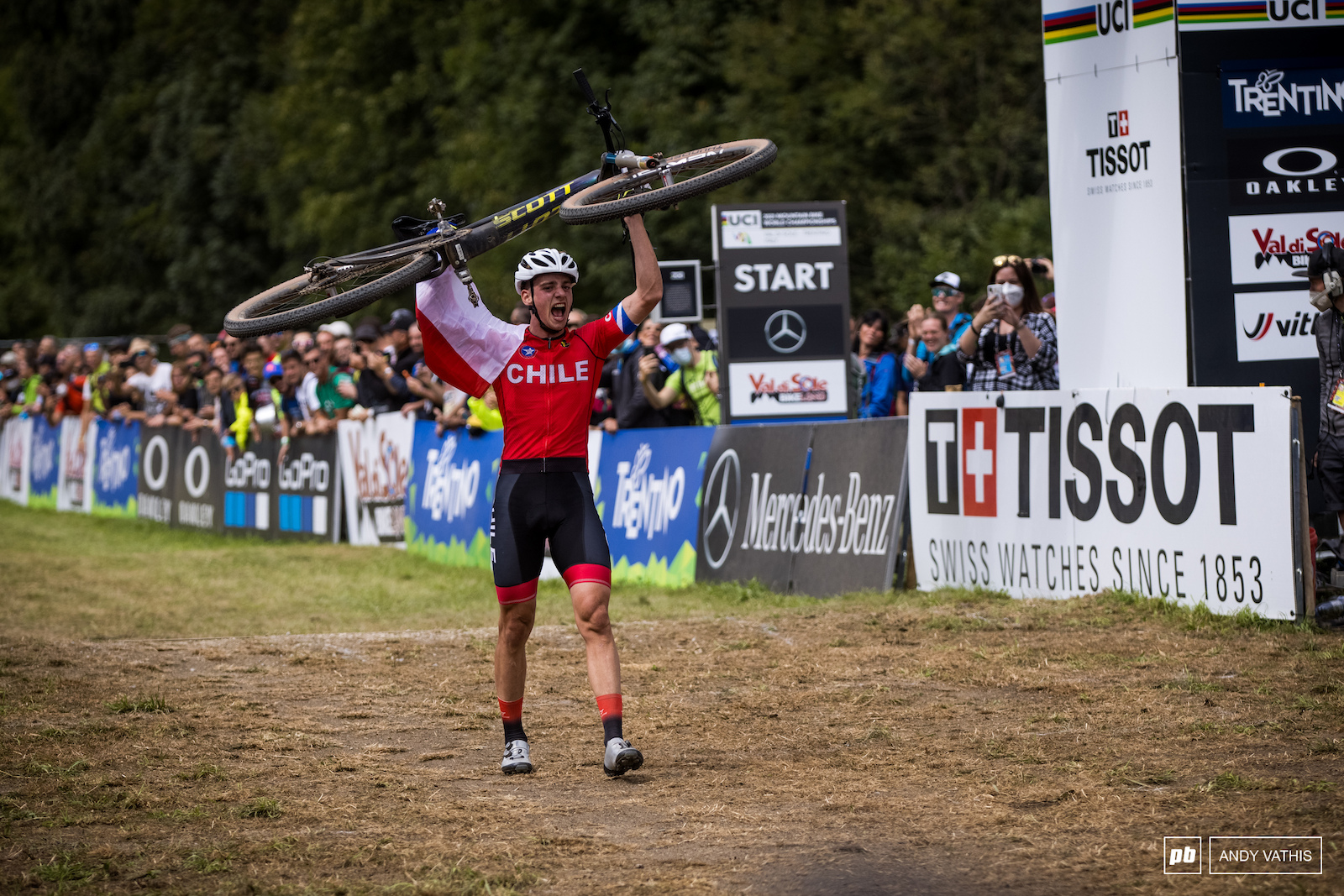 Martin Vidaurre Kossmann across the line with bike way in the air.