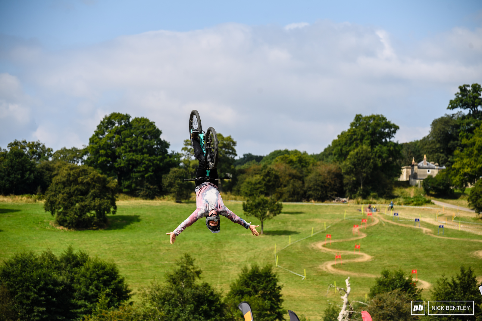 Zac Rainbow pulling a Tuck No Hander Back Flip into the stunning Eastnor Deer Park view